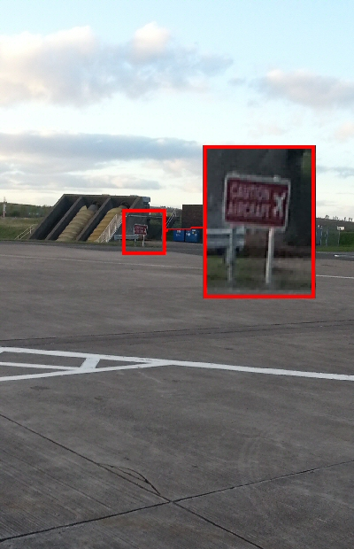 "Picture of runway with sign ""danger aircraft"""
