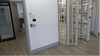 Gym doors: A highly secure turnstyle on the right, with an open door on the left.