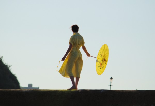 Girl in yellow on St Andrews harbour wall.