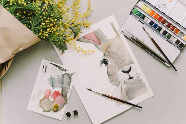 easter bunny painting and watercolor palette on white surface