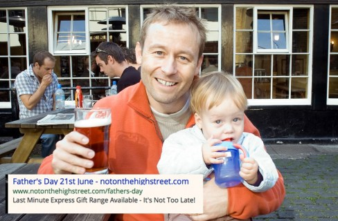 smiling man holding a child and a pint of beer