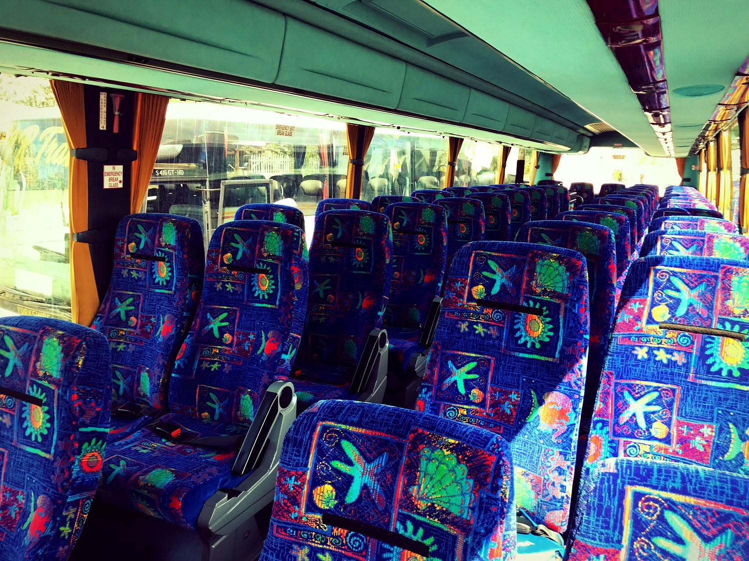 A view of the seats in Advanced Travel's 49 seater Scania Irizar coach, which is available for coach hire in Sheffield. The seats are reclinable and have lap belts. They are covered in a blue fabric with a seashell pattern. There are two rows of double seats with an aisle down the middle. There are two rows of overhead storage compartments above each row of seats.