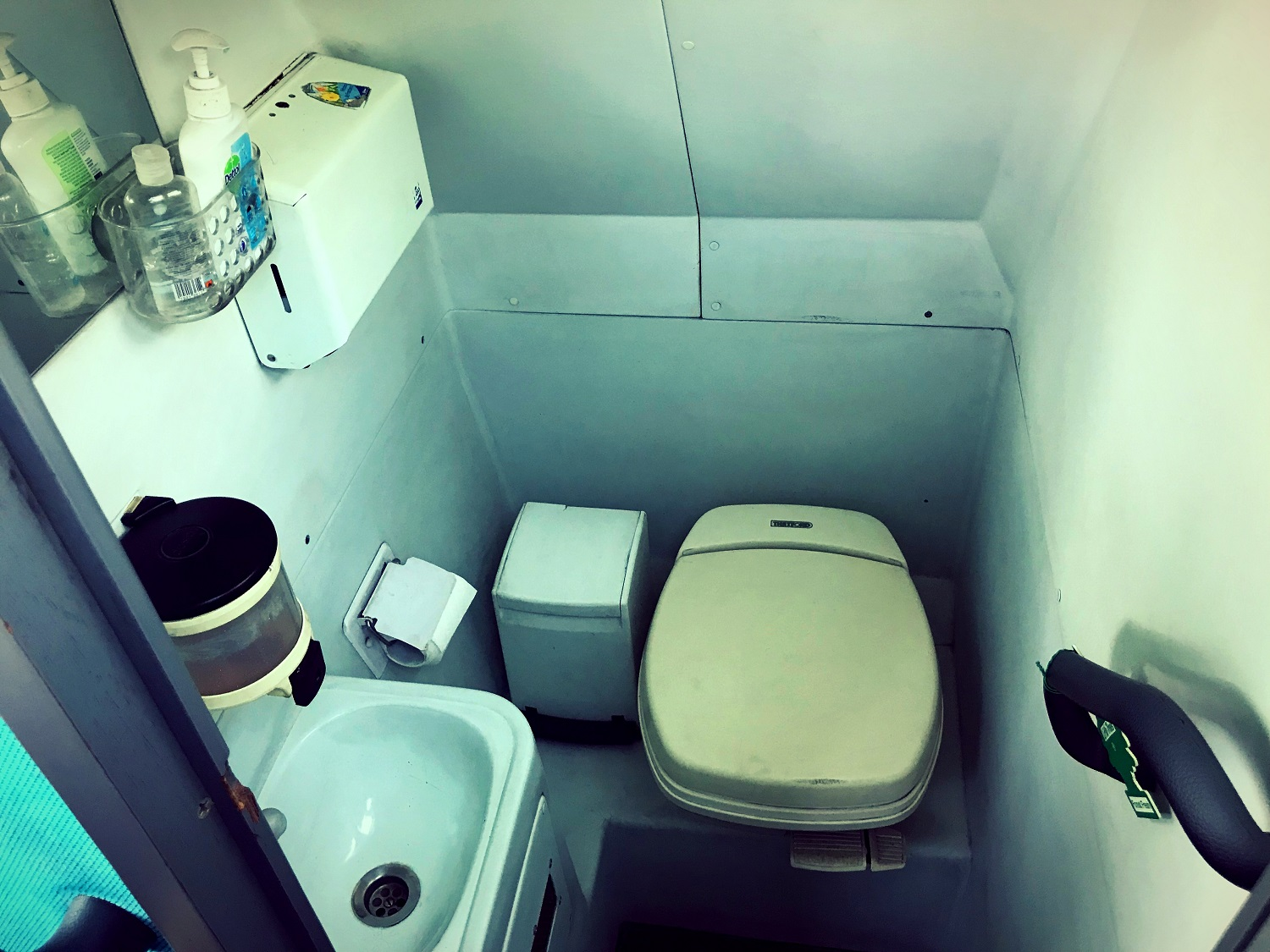 A view of the toilet in Advanced Travel's 49 seater Scania Irizar coach, which is available for coach hire in Sheffield. There is a small cubicle with a hand rail leading into it. There is a toilet, toilet roll dispenser, sink, soap dispenser and hand towel dispenser. There is also a waste paper bin and some additional soaps and cleaning products. There is a small mirror above the sink.