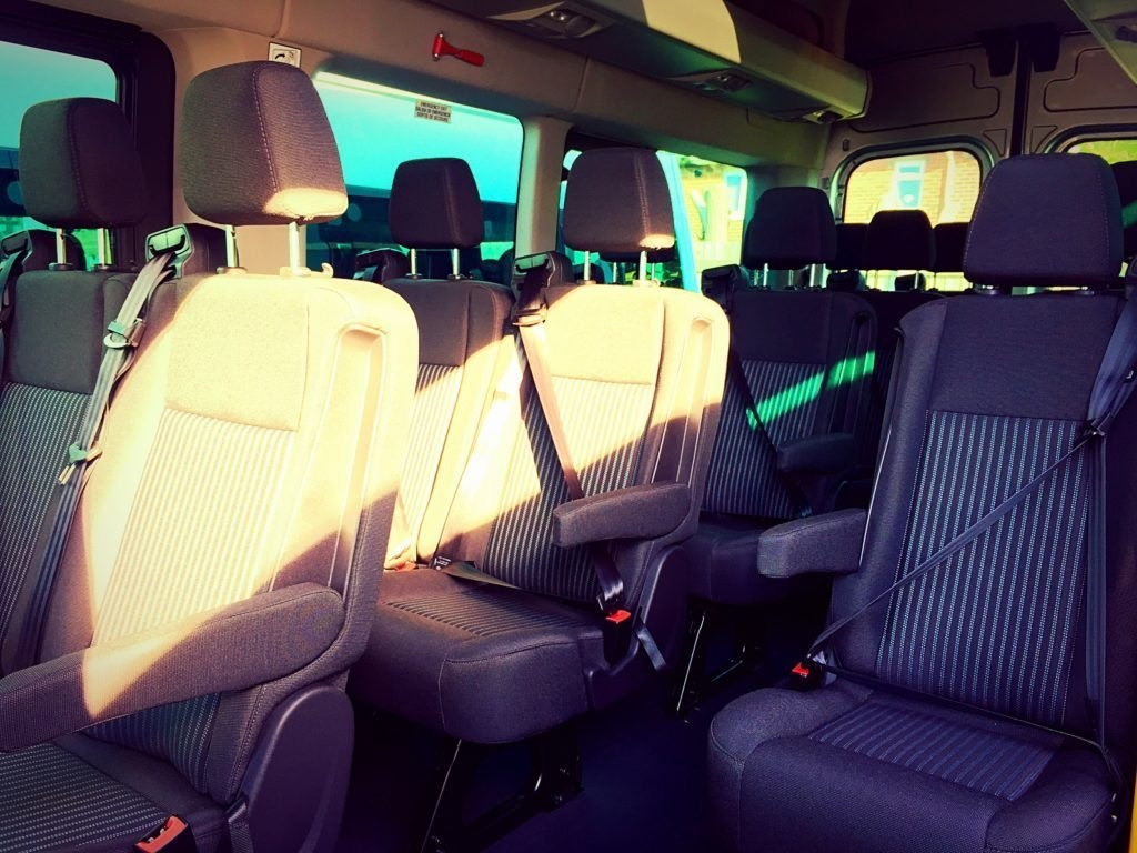The seats in Advanced Travel's 16 Seater Ford Transit minibus, which is available to hire from Doncaster. There is one row of single seats on the right hand side, an aisle in the middle, and then a row of double seats on the left hand side. The seats all have arm rests, head rests and three-point seatbelts. They are made of a grey material with, with a grey and white striped material covering the middle portion of the seat and backrest. There is an overhead storage shelf above the seats. There are adjustable dials and fans for the air-conditioning, and reading lights and their switches above the seats.