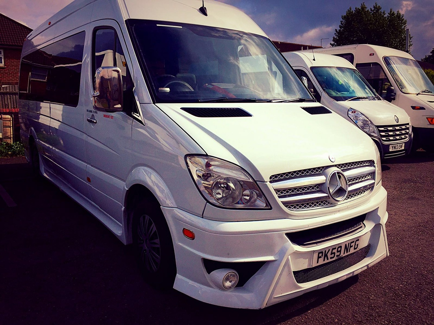 The outside of our Luxury Mercedes Sprinter 16 Seater Minibus. The minibus is white with tinted passenger windows.