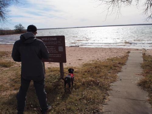 Man and black dog wearing red vest in Foss Park