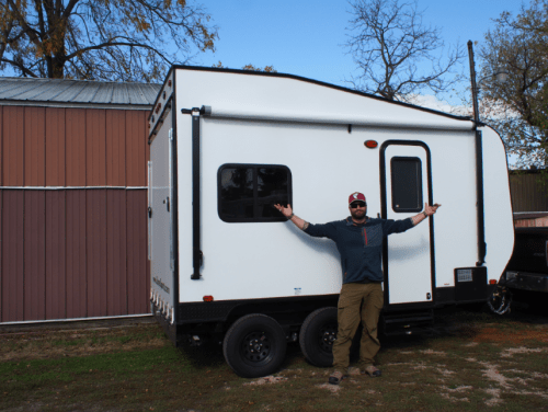 man standing in front of a small camper