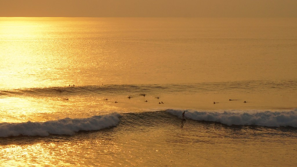 Pro surfers catching some evening waves at Uluwatu Beach