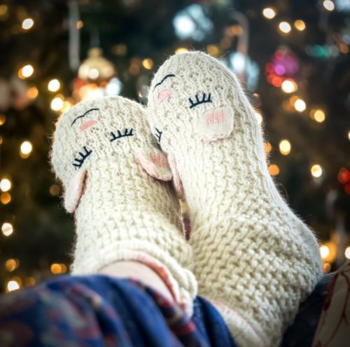 Feet with fuzzy bunny slippers in front of a christmas tree.