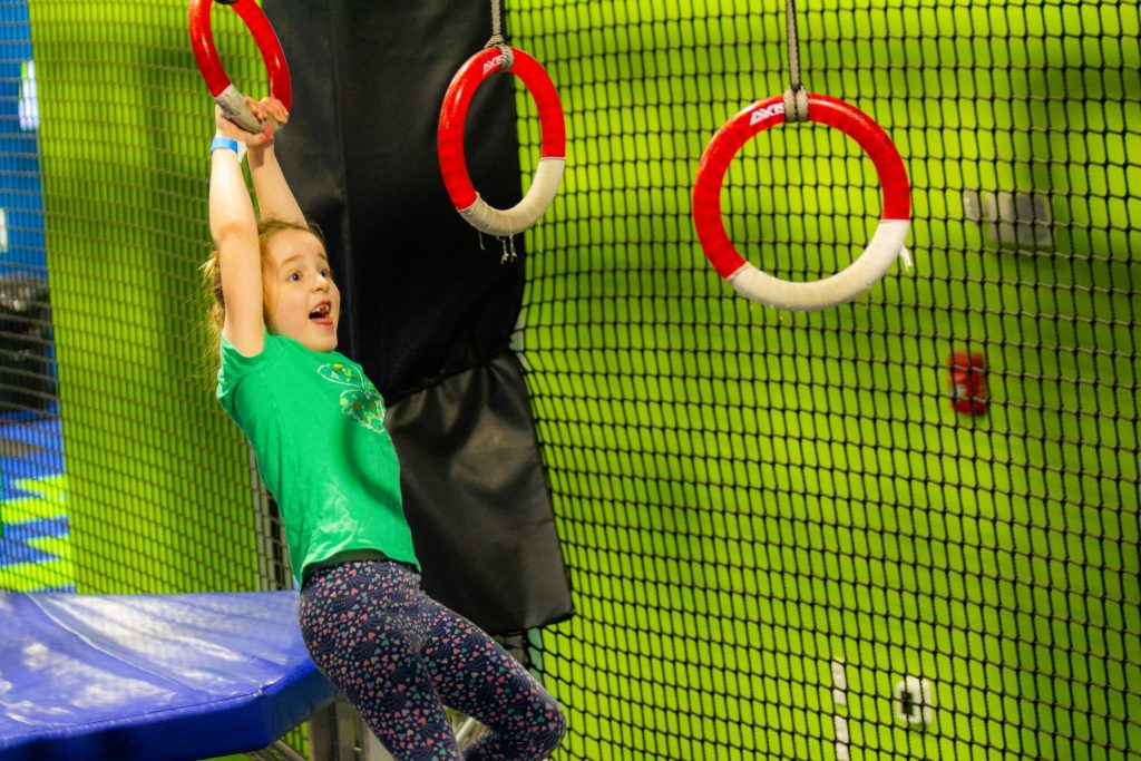 girl swinging on rings