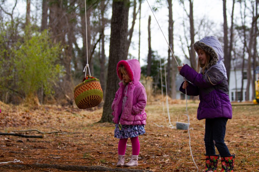 sisters playing with pulley at Tinkergarten