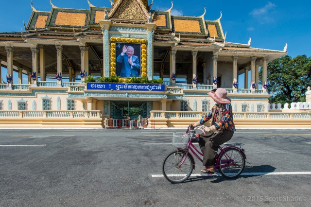 Woman rides bicycle on the grounds of the Royal Palace in Phnom Penh