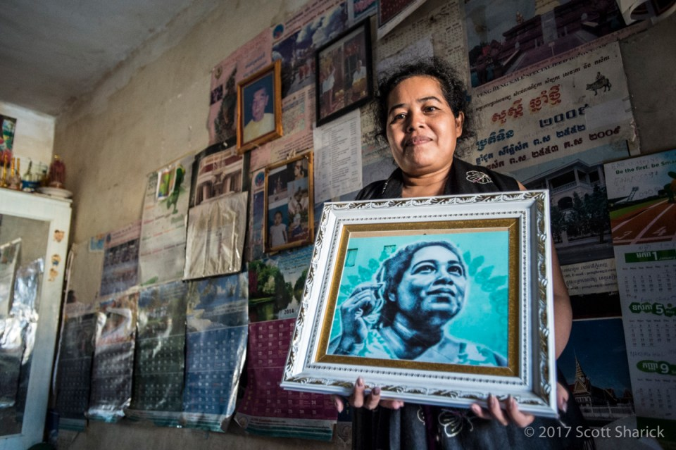 Moeun Thary holds the image that was painted on the north wall of the White Building in Phnom Penh, Cambodia