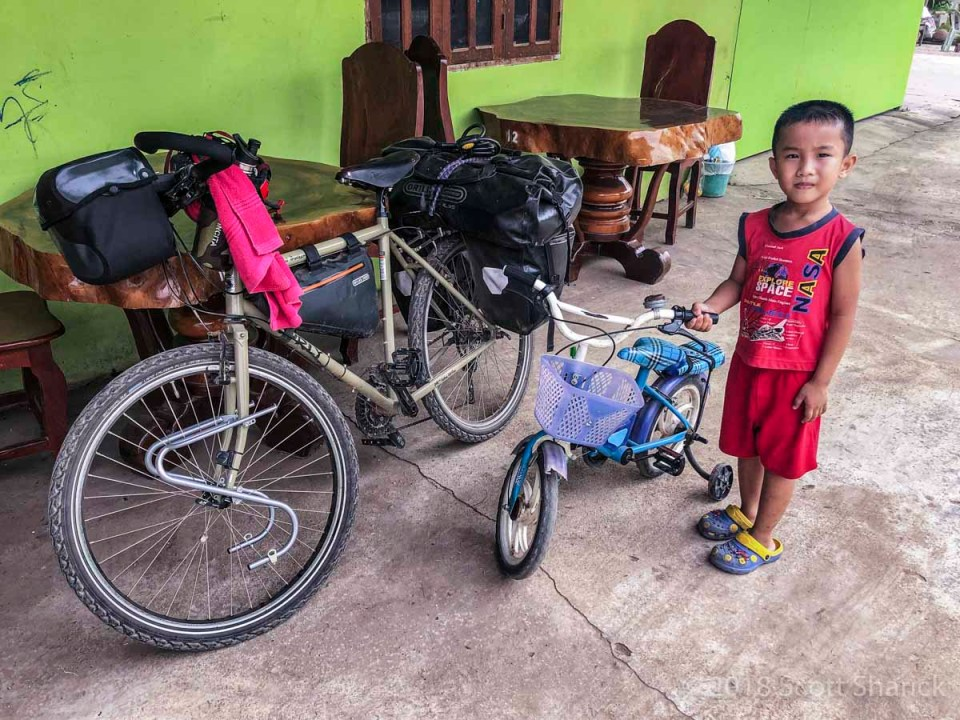 A young Khmer boy stands next to my bicycle with his training-wheel equipped pint-sized bicycle