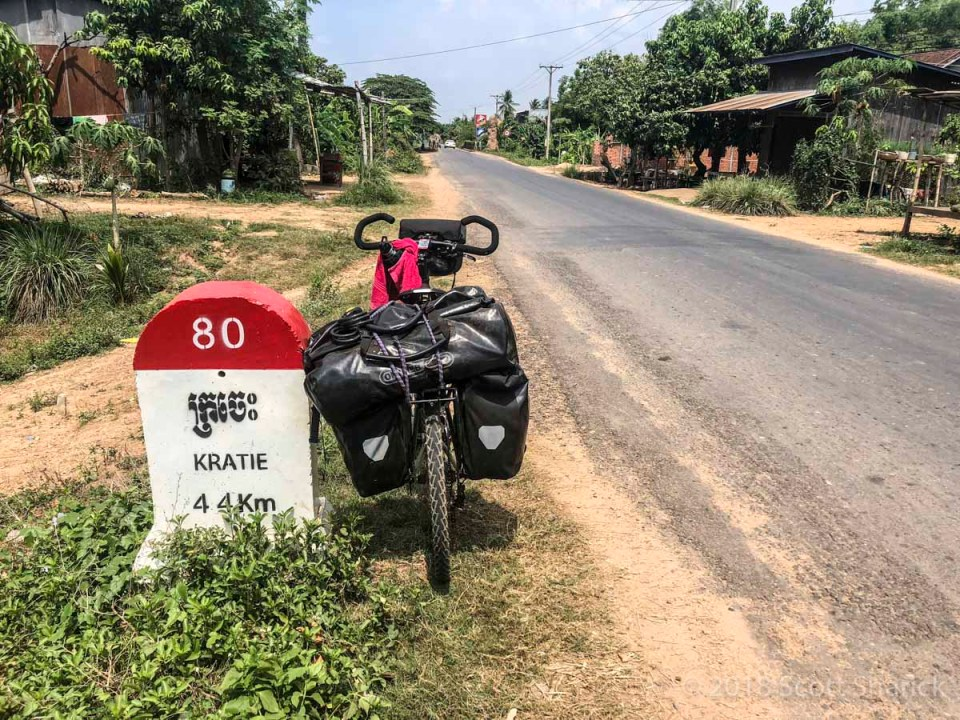 My loaded bicycle leans against a roadside marker stating Kratie is 44 kilometers ahead.