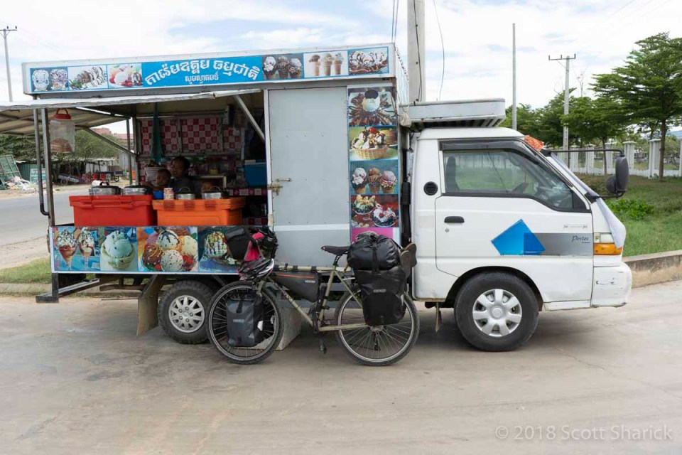 My loaded bicycle leans against an ice cream truck parked outside a factory in Cambodia.