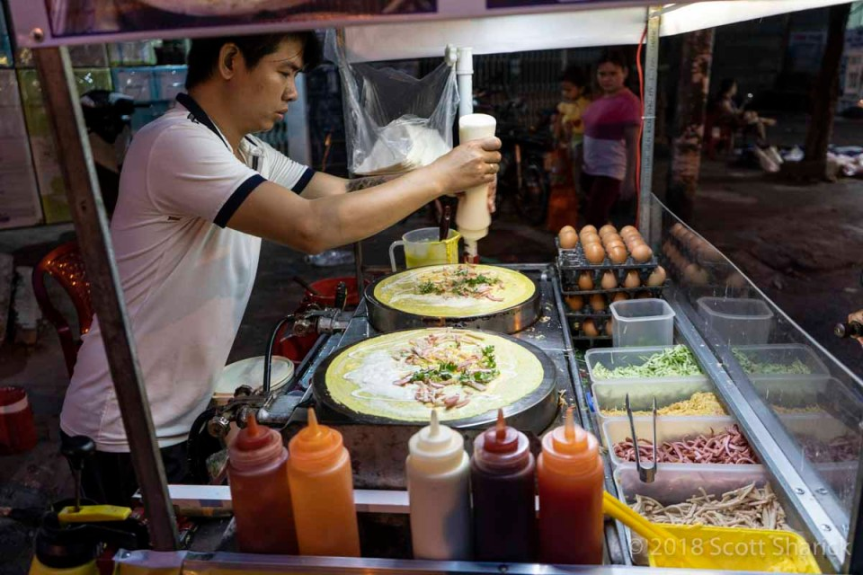 A Vietnamese man adds ingredients to his pancakes in his food stall in Rach Gia, Vietnam.