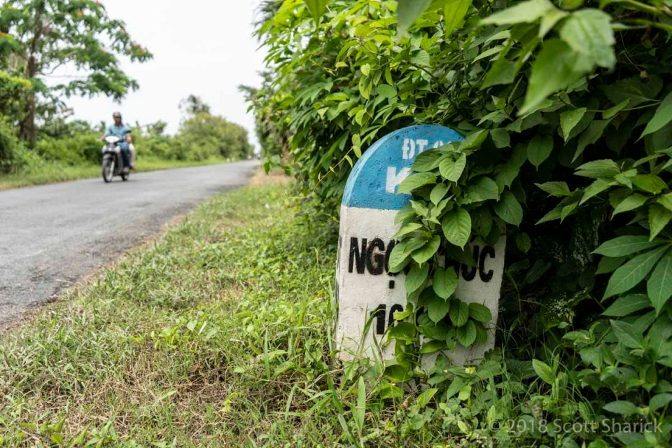A roadside marker on a quiet country road in Vietnam.