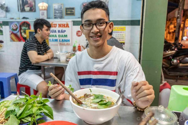 A young Vietnamese man eating Pho in a restaurant in Can Tho, Vietnam.