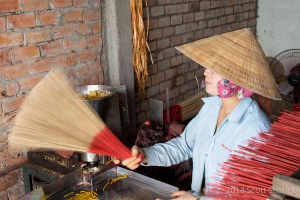 Vietnamese woman shaking the incense sticks before the incense is applied.