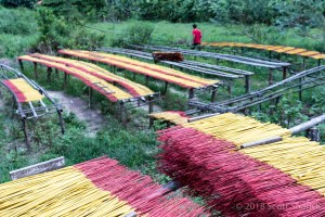 Freshly made incense is dried on stands on the side of the road in Vietnam.
