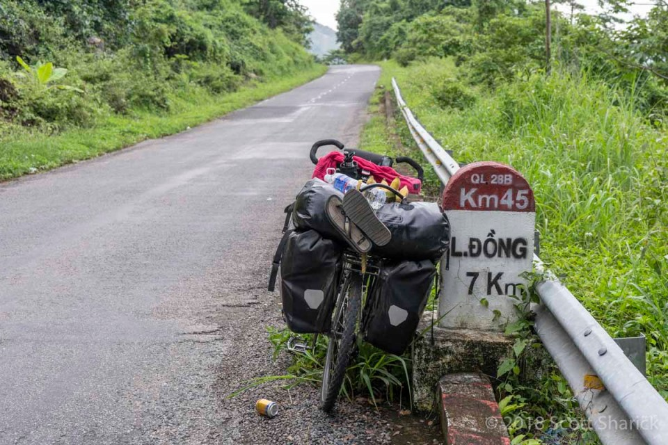 My fully loaded bicycle leans against a roadside marker on the way up the mountains to Dalat, Vietnam.