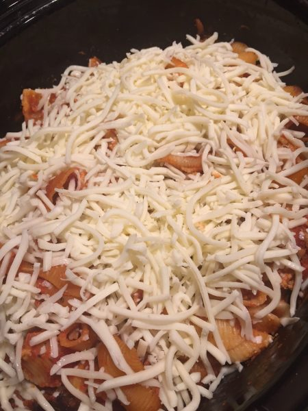 After your sauce and shells have cooked, it's time to add mozzarella cheese to your slow cooker lasagna casserole. A deliciously easy meal that tastes just like grandma's lasagna. A quick weeknight meal sure to become a family favorite. - Adventures of B2