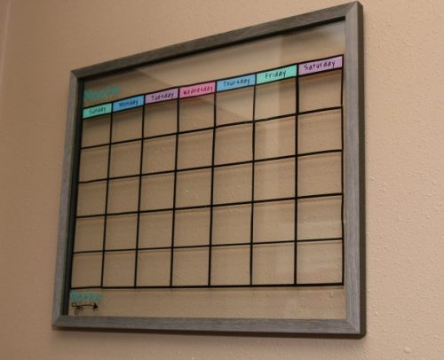 DIY dry erase calendar hung on wall. Using a floating photo frame, this DIY calendar is so simple to make and keeps your life organized.