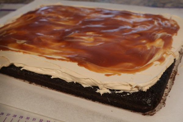 Chocolate cake with caramel icing and caramel sauce on top.