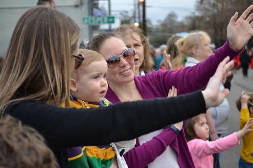 A mom showing her baby how to catch beads at Mardi Gras! Are you heading to New Orleans for Mardi Gras with kids? Get the most out of your trip with these helpful tips! - Adventures of B2