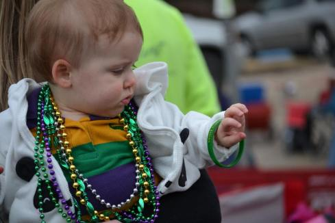 A baby admiring her bracelet she caught of a float at Mardi Gras in New Orleans. Learn all the best tips of surviving mardi gras with kids at Adventuresofb2.com