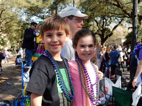 two kids enjoying Mardi Gras parades in New Orleans. Learn how to make your trip with kids to Mardi Gras successful at adventuresofb2.com