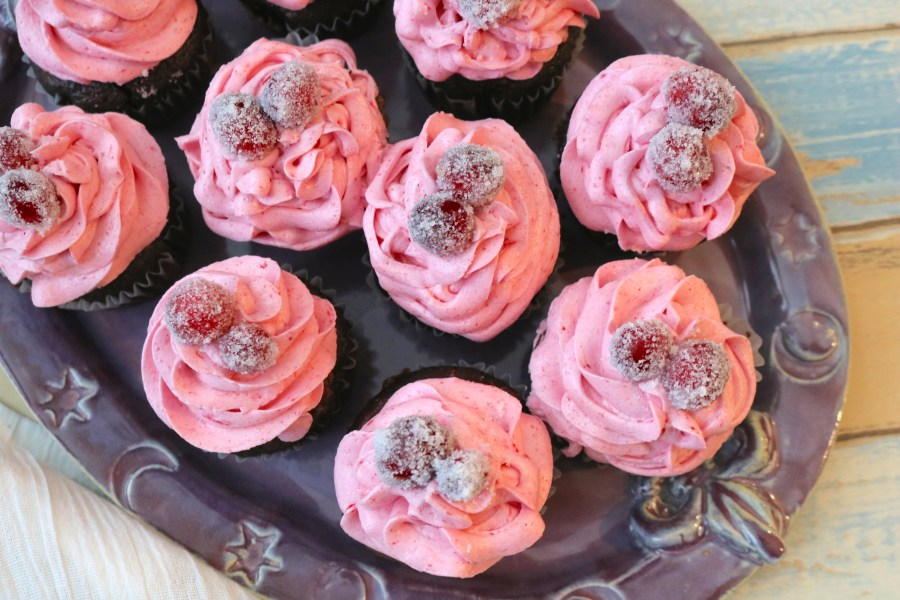 How fabulous do these Sparkling Cranberry Chocolate Cupcakes look? A moist delicious chocolate cupcake with sweet cranberry buttercream and topped with sugared cranberries. Surprise your spouse with this romantic dessert. - Adventures of B2