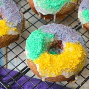 Gluten free king cake donuts cooling on a rack with fresh icing and colored sugar on top! A satisfying breakfast to jazz up your mardi gras season. - Adventuresofb2.com