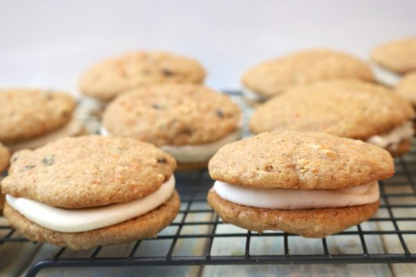 Amazingly delicious carrot cake whoopie pies are the most delicious cookie to bring to any party! a soft fluffy cookie with flavors of carrot cake and hints of cinnamon. Sandwiched in between is a sweet cream cheese filling to complete this delicious carrot cake dessert! - Adventuresofb2.com