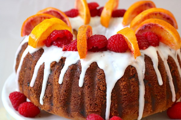 Raspberry and Blood Orange Bundt Cake is a simple yet picture worthy homemade bundt cake recipe that will have all your guest drooling! A moist bundt cake filled with flavors of sweet blood oranges and raspberries. Topped with a blood orange glaze and garnishes to take this cake recipe to the next level! - Adventuresofb2.com