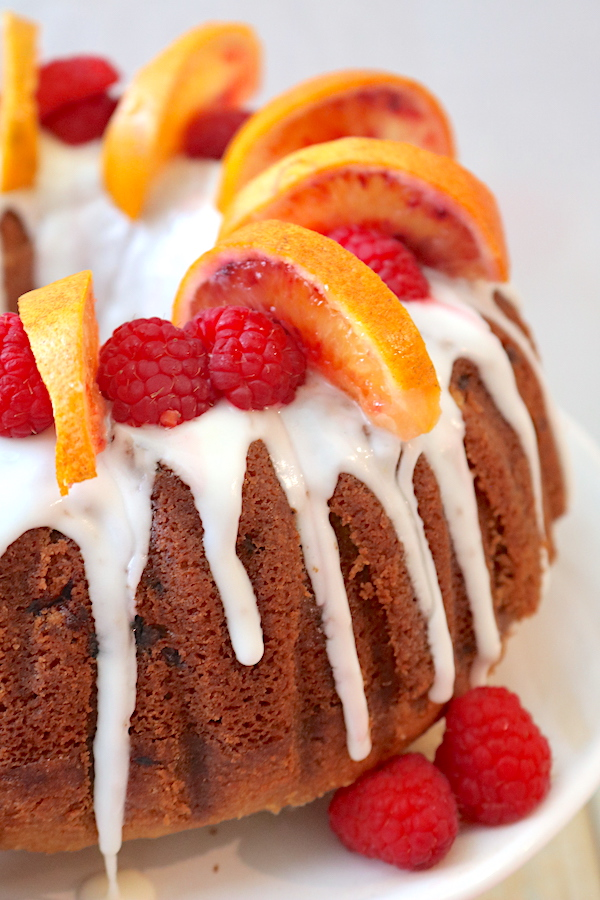 Raspberry and Blood Orange bundt cake is an easy cake recipe for anyone to make. Full of flavor and picture worthy! This moist bundt cake is filled with flavors of sweet blood oranges and raspberries topped with a blood orange glaze. Perfect for any holiday celebration! - Adventuresofb2.com
