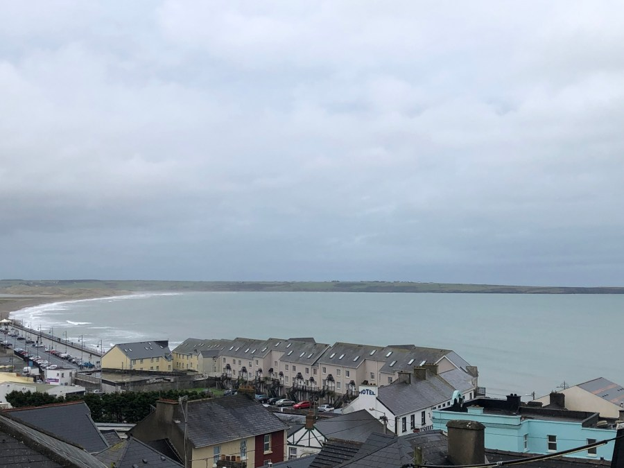 On the coast of Tramore in Waterfored, Ireland. This pleasant, peaceful city is full of colorful houses on a hill and beaches for days! A beautiful stop for an Ireland road trip- Adventuresofb2.com
