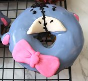 The finishing touches for making a doughnut look like Eeyore is placing fondant pink bow and tiny ovals for the ears. Add a moustache shaped nose. Then pipe black icing for the hair. Add a line from the hair down through the nose and put little lines on each side to make it look like stitching. Last, add small dots for the eyes and small lines for the eyebrows and nostrils. - adventuresofb2.com