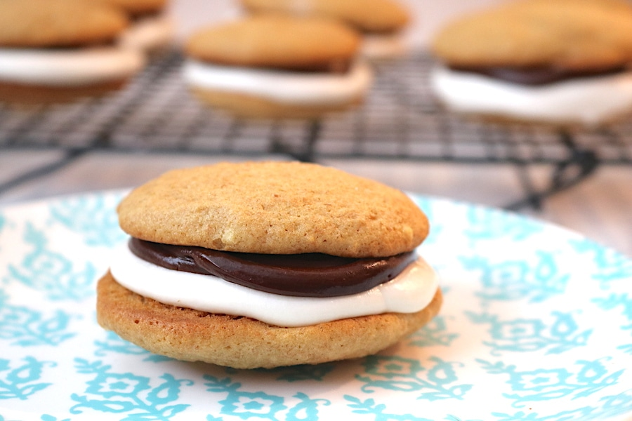 The ultimate way to eat a s'mores. S'mores Whoopie Pies are made of a soft graham cracker cookie with smooth chocolate ganache and fluffy marshmallow buttercream. Easy to make and kid approved, these will be the perfect winter dessert for cold nights! Pairs perfectly with a nice cup of hot coca- adventuresofb2.com