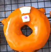 Once the orange base of the Tigger doughnut has dried, add a trapezoid and small square piece of fondant for the eyes and nose of Tigger. Add a small pink circle of fondant for the nose. - Adventuresofb2.com