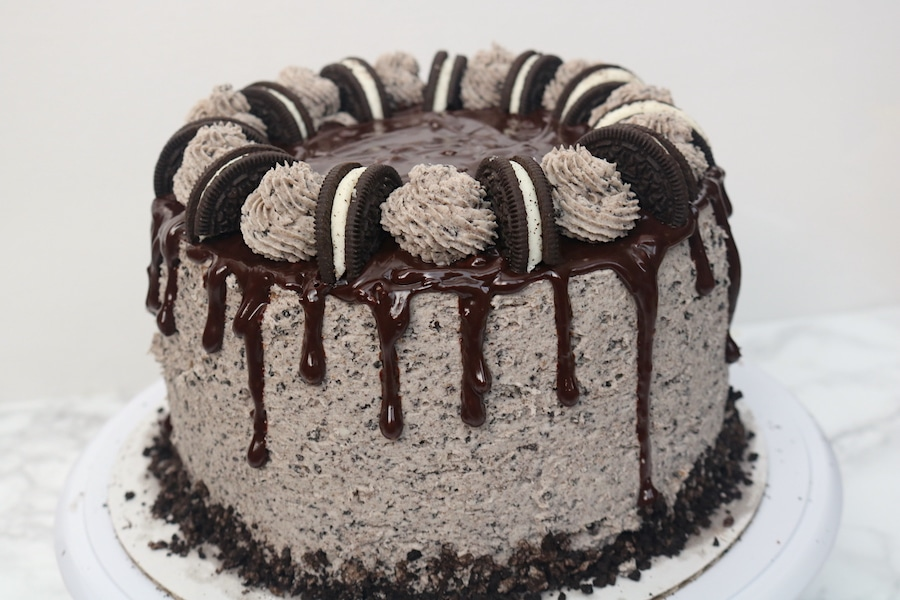 Oreo cookies n cream cake is the perfect celebration cake! It is loaded with Oreo cookies. It's a 3 layer simple white cake with bits of cookies and cream with oreo buttercream layered in between with chocolate ganache. It's every cookie lover's dream! - adventuresofb2.com
