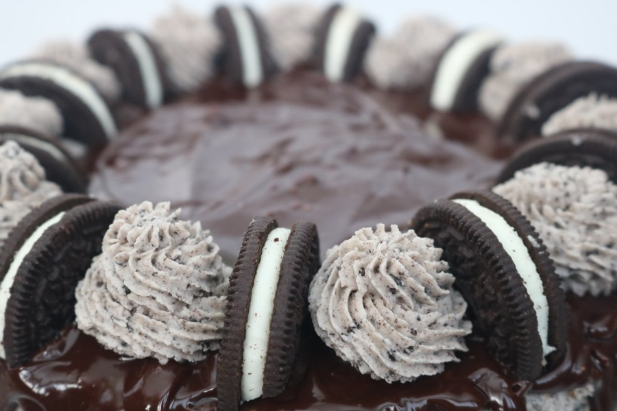 The perfect party cake for any occasion. Oreo cookies and cream layer cake is the perfect celebration cake! It is loaded with Oreo cookies. It's a 3 layer simple white cake with bits of cookies and cream with oreo buttercream layered in between with chocolate ganache. It's every cookie lover's dream! - adventuresofb2.com