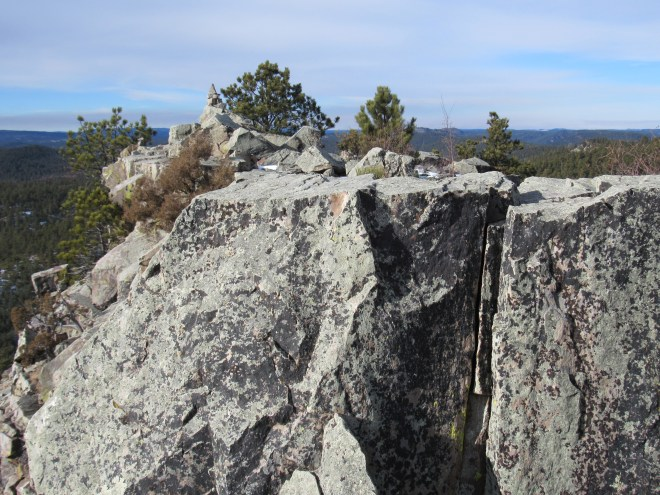 The summit cairn is now clearly in sight beyond the upper portion of the rock wall blocking Lupe's advance.
