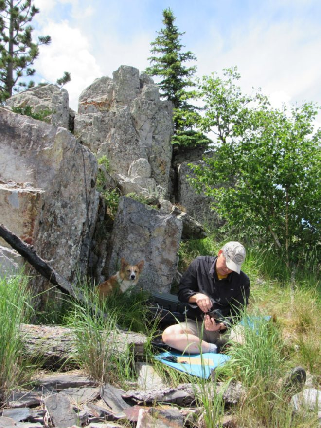 Lupe supervises from the shade while Joe sets up his portable ham radio NE of a jagged rock outcropping NW of the ranger station.