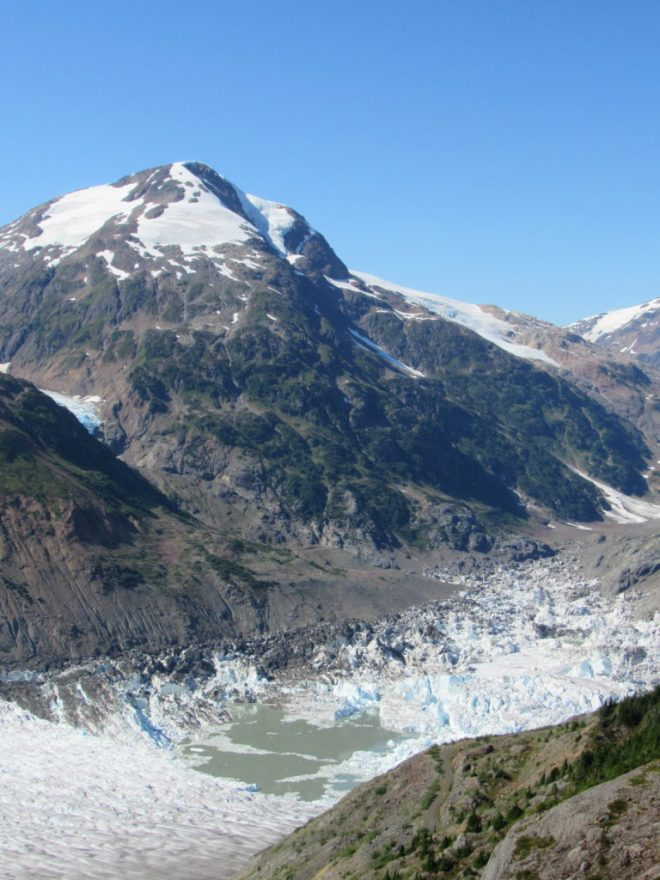 Lupe saw this view of the gray green waters surrounded by collapsed snow and ice remaining after the natural draining of Summit Lake under the Salmon Glacier in July. It's easy to see the typical high water line of Summit Lake along the base of the mountain slope on the L. Photo looks NW.