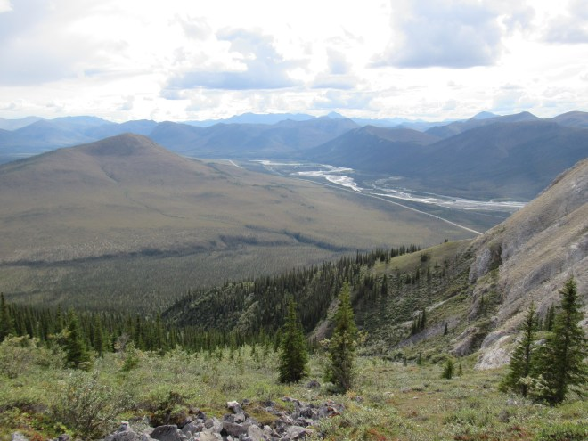 View looking back from the main S ridge. High point 2929 is the big barren hill on the L. The lower minor S ridge of Sukakpak is in view on the R. The Dalton Highway and Middle Fork of the Koyukuk River are seen in the distance. Photo looks SW.