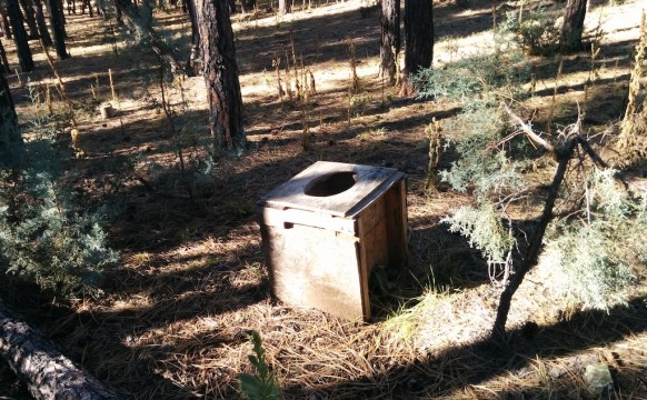a wooden toilet box in the middle of nowhere