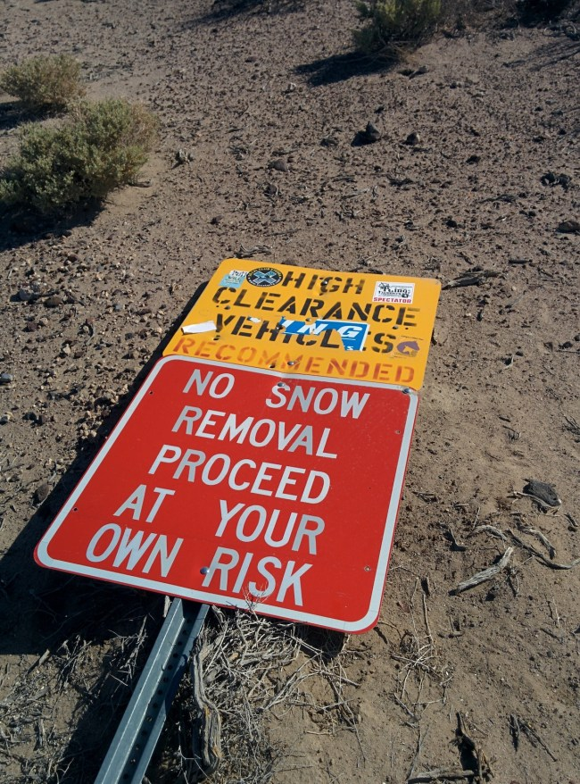 "Sign on ground warning that high clearance vehicle will not happen so ""proceed at your own risk""s are recommended and that snow removal"