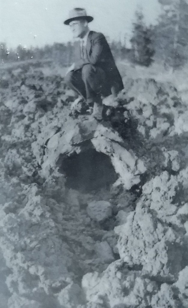 Man in the 1940's sitting on a lava cast